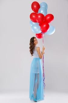 多くのカラフルな風船で美しいドレスを着ている女性