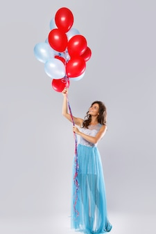 Woman wearing beautiful dress with a lot of colorful balloons
