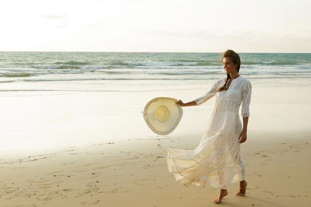 美しい白いドレスを着ている女性は日没時にビーチを歩いています。