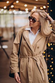 クリスマスにベージュのコートを着て通りを歩いている女性