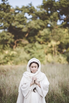 Woman wearing a biblical robe and praying while her eyes are closed