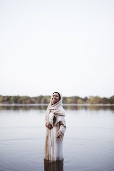Woman wearing a biblical robe while standing in the water and smiling