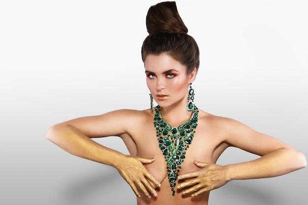 多くの宝石と大きな美しいネックレスを着ている女性