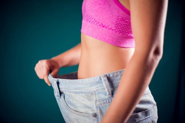 大きなサイズのジーンズを着ている女性。減量、フィットネス、ダイエットのコンセプト