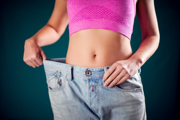 Woman wearing big size jeans. weight loss, fitness and diet concept