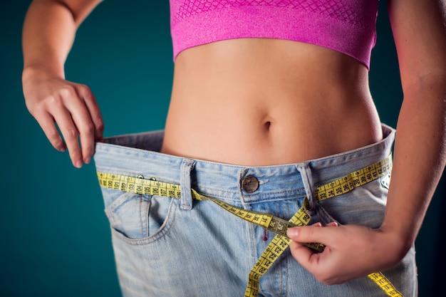 ベルトにメーターが付いた大きなサイズのジーンズを着ている女性。減量、フィットネス、ダイエットのコンセプト