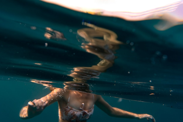 Женщина в бикини купается в океане
