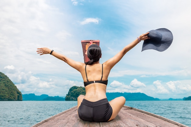 Woman wearing bikini sitting on the boat with hands up and holding sunhat enjoy vacation.