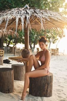 Женщина в бикини сидит в баре на пляже