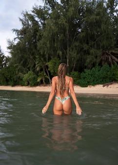 Woman wearing bikini and sitting in water next to beach