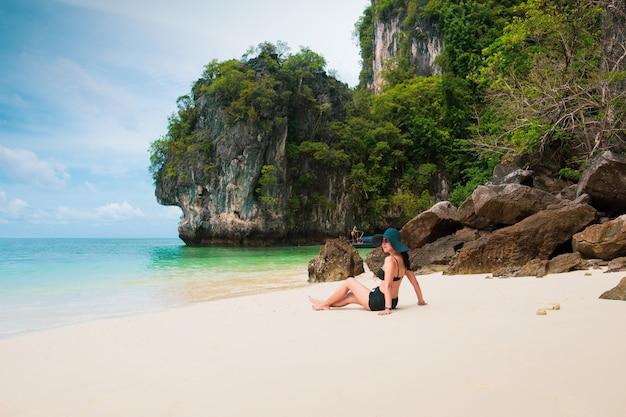 모래 해변에 siting 비치 모자와 비키니를 입고 여자는 휴가를 즐길 수 있습니다.
