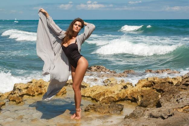 岩のビーチで黒のボディースーツと美しいシルクのドレスを着ている女性