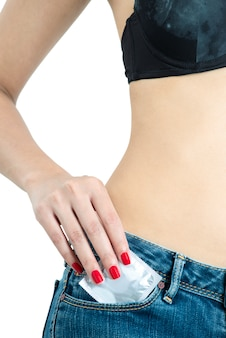 Woman wearing black bra and jeans with red nails pick condom package to pocket isolated on a white background