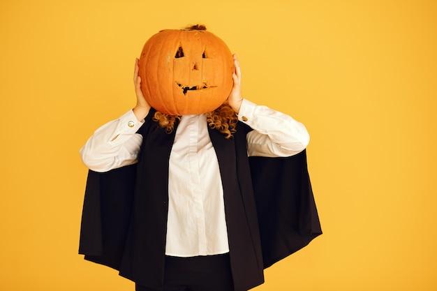 Женщина в черном костюме. дама с хеллоуинским макияжем. девушка стояла на желтом фоне.