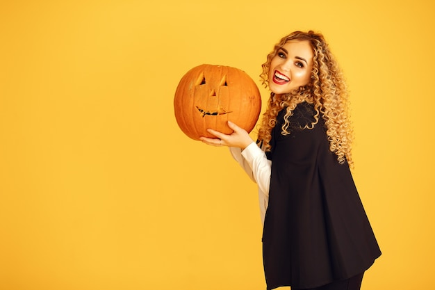 Woman wearing black costume. lady with halloween makeup. girl standing on a yellow background.