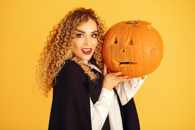 Donna che indossa il costume nero. signora con trucco di halloween. ragazza in piedi su uno sfondo giallo.