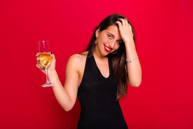 Donna che indossa un abito nero e che tiene un bicchiere di champagne in posa sul rosso