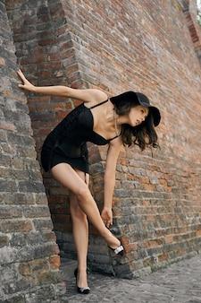 Женщина в черном платье позирует возле кирпичной стены.