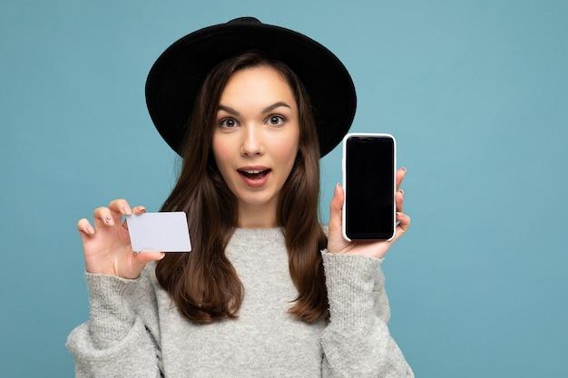 Женщина в черной шляпе и сером свитере изолирована на синей стене, держит кредитную карту и мобильный телефон с пустым дисплеем