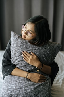 Woman wearing a black robe, hugging pillow in bed.