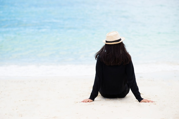 Woman wearing black shirt and straw hat sitting on the sand