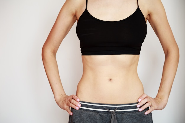 Woman wearing black sport bra and gray pants with slim body