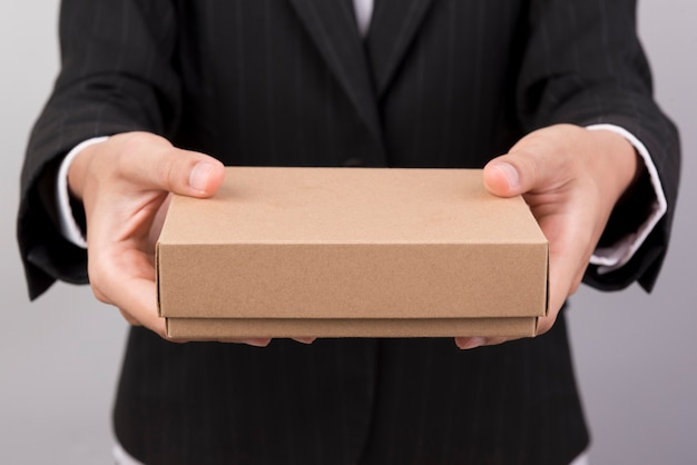 A woman wearing a black suit extends a brown gift box.