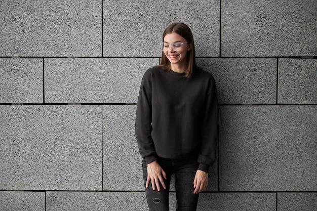 모의, 로고 디자인 또는 디자인 인쇄를 위해 검은 색 셔츠 또는 까마귀를 입은 여성은 도시 거리에 여유 공간이 있습니다.