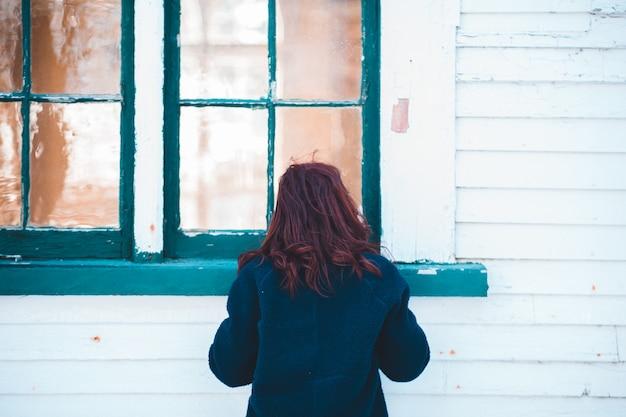 Женщина в синем пальто стоит возле окна