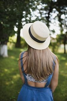 公園で青いドレスと白い帽子をかぶった女性