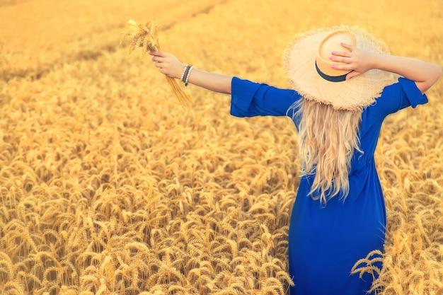 Женщина в синем платье в пшеничном поле