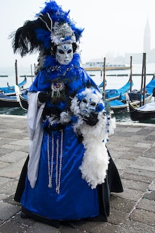 Woman wearing blue dress with boa poses on the venetian lagoon during carnival in venice