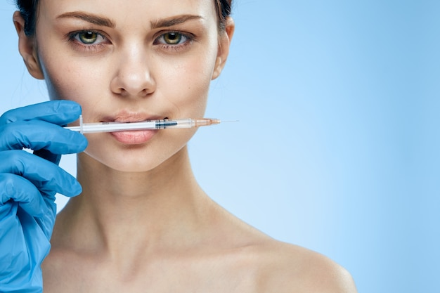 Женщина в синих перчатках со шприцем для лечения морщин с помощью инъекций ботокса