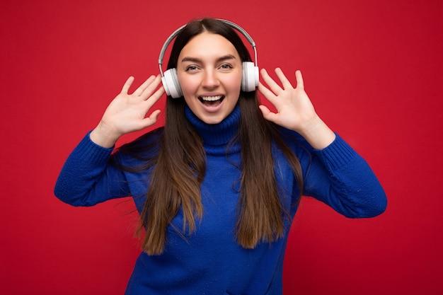 빨간색 배경 위에 절연 파란색 스웨터를 입고 여자 멋진 음악을 듣고 카메라를보고 재미 흰색 블루투스 이어폰을 입고 벽.