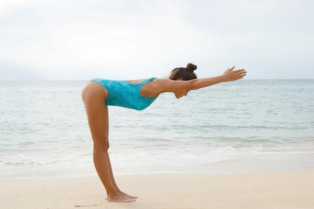 해변에서 요가 연습을 하 고 파란색 수영복을 입고 여자