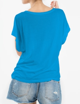 Woman wearing blue t-shirt and short rip jeans on white