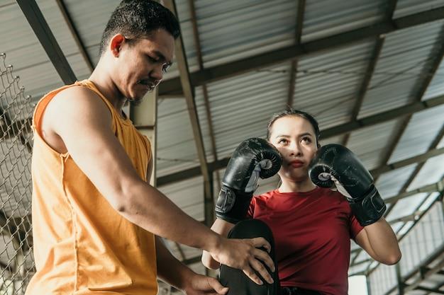 권투 링에 서있는 그녀의 트레이너와 함께 권투 장갑을 끼고 여자