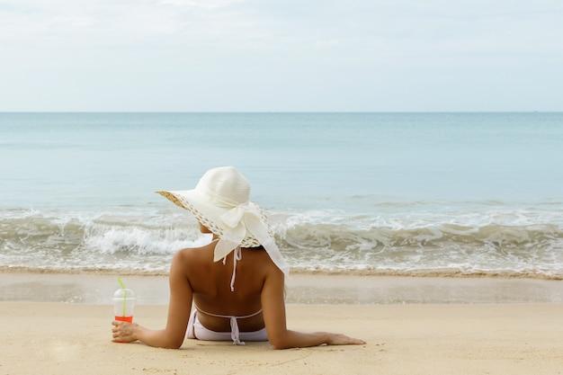 Женщина в широкополой шляпе держит стакан холодного коктейля и сидит на пляже