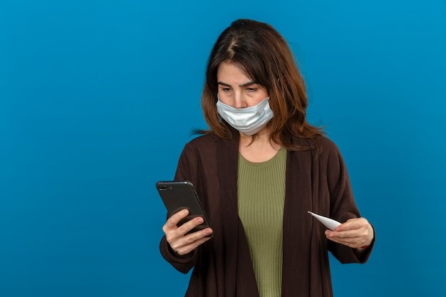 孤立した青い壁に神経質に見える誰かを呼び出す手でスマートフォンとデジタル温度計を保持している医療用防護マスクで茶色のカーディガンを着ている女性