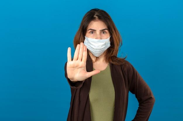Женщина в коричневом кардигане в медицинской защитной маске стоит с открытой рукой и делает знак остановки с серьезным и уверенным выражением лица, защищая жест над изолированной синей стеной