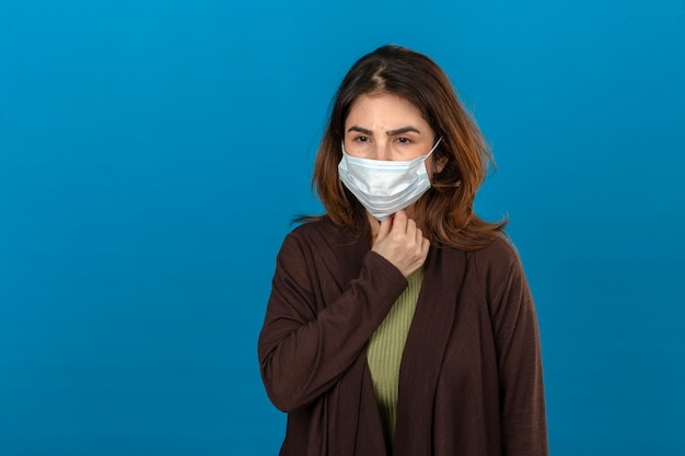 Woman wearing brown cardigan in medical protective mask looking sick touching neck suffering from pain standing over isolated blue wall