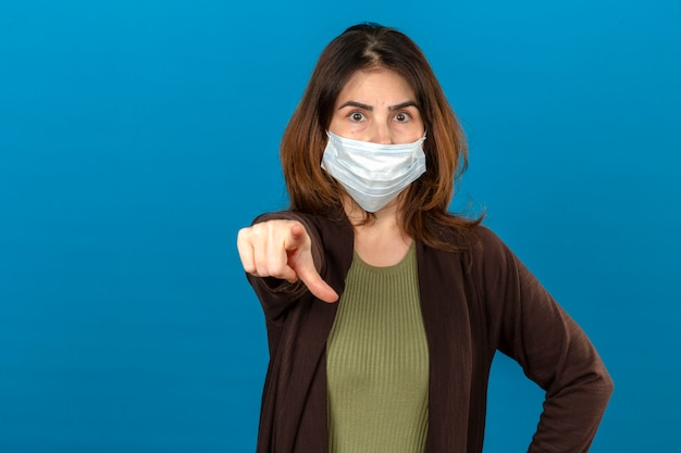 Woman wearing brown cardigan in medical protective mask pointing displeased and frustrated to the camera angry and furious with you over isolated blue wall