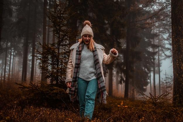 Женщина в коричневой вязаной шапке в лесу