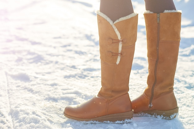 Woman wearing brown winter boots on the snow