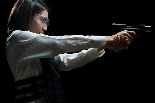 Woman wearing bulletproof vest shoots with gun at a target at indoor gun range.
