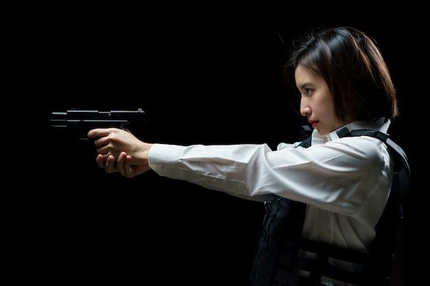 Woman wearing bulletproof vest shoots with gun at a target at indoor gun range.