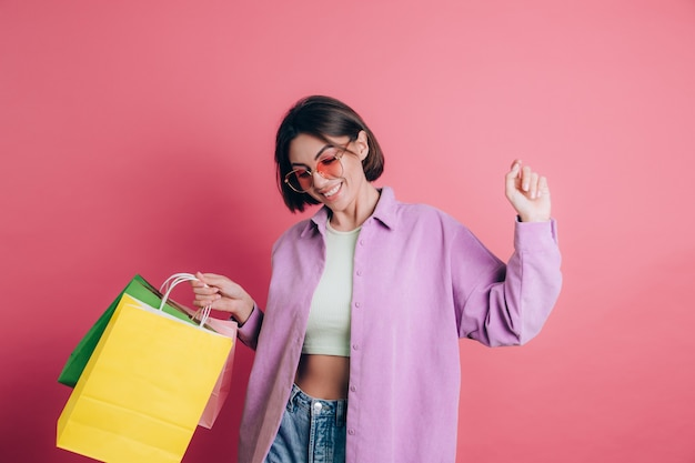 Woman wearing casual sweater on background happy enjoying shopping holding colorful bags wearing summer sunglasses