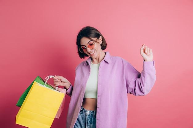 Donna che indossa un maglione casual su sfondo felice godendo dello shopping tenendo i sacchetti colorati indossando occhiali da sole estivi