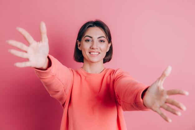 Donna che indossa un maglione casual su sfondo guardando la telecamera sorridendo con le braccia aperte per abbraccio