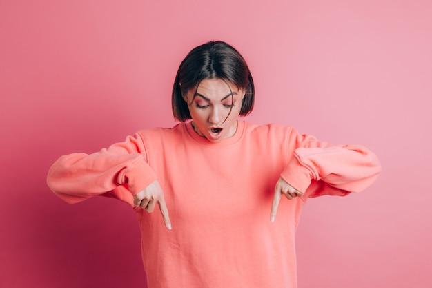 Donna che indossa un maglione casual sullo sfondo con la punta rivolta verso il basso con le dita che mostrano pubblicità, volto sorpreso e bocca aperta